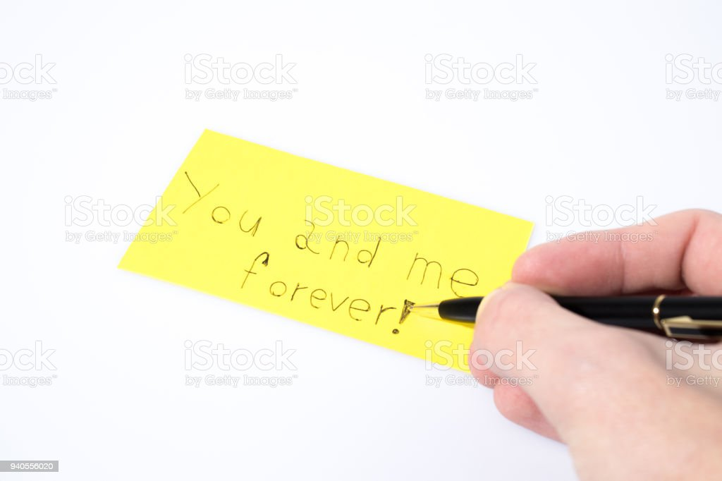You and me forever handwrite witha a pen and a hand on a yellow paper composition stock photo