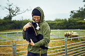 Shot of a cheerful young farmer holding his young little sheepdog puppy in his arms outside during the day