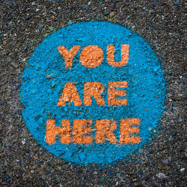 You Are Here. Funny, Obvious Circular Public Park Sign Painted on Pavement. stock photo
