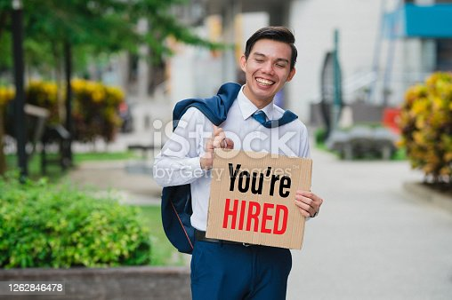 Happy Young Asian businessman in suit holding card sign you are hired at city street,
