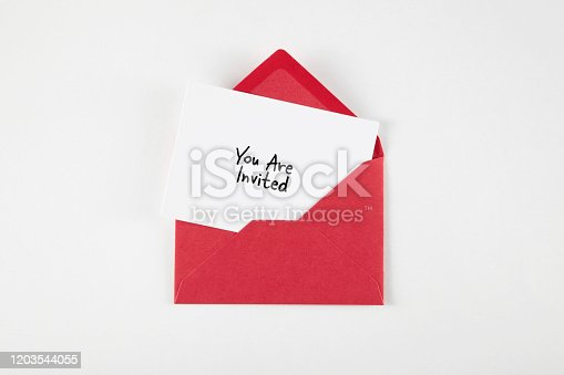 You Are Invited note in red envelope. Isolated on white.