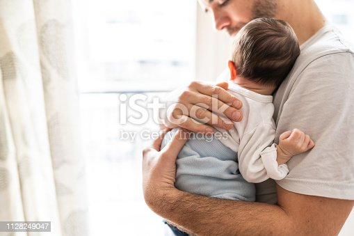 Affectionate love between father and newborn baby, father holding his son in arms in apartment