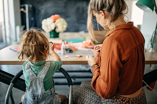 Mother and daughter making flowers of paper