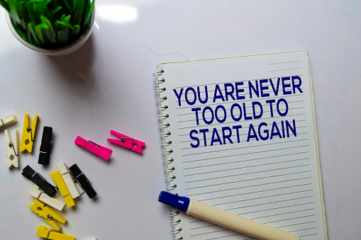istock You Are Never Too Old To Start Again text on a book at office desk. Motivation concept 1187921120
