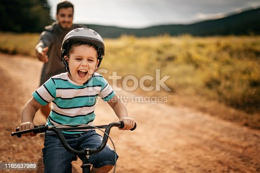 Father helping son to ride a bicycle