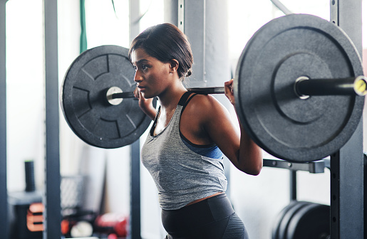 Cropped shot of a young woman working out with a barbell at the gym