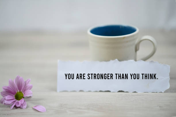 You are stronger than you think, a paper note with morning coffee. Inspirational quote - You are stronger than you think. With a cup of morning coffee and beautiful purple daisy flower on white wooden table background. Motivation words on paper note with motivating text concept. encouragement stock pictures, royalty-free photos & images