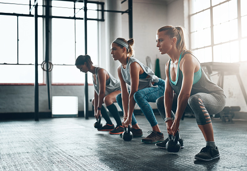 Shot of three young women working out together