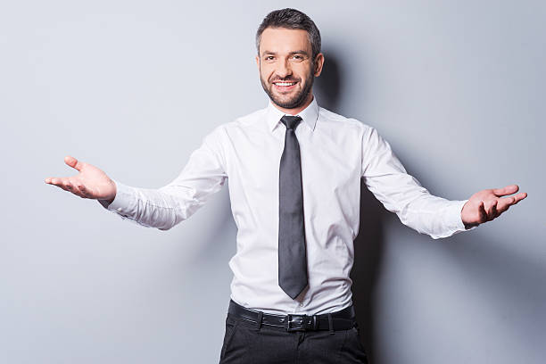 You are welcome! Cheerful mature man in shirt and tie gesturing welcome sign and smiling while standing against grey background arms outstretched stock pictures, royalty-free photos & images