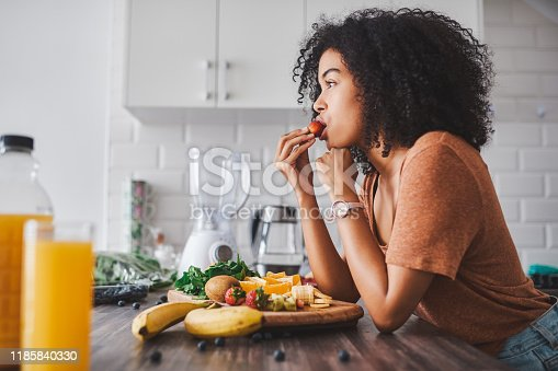 Shot of a young woman making a healthy snack with fruit at home