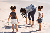 Shot of young mother making a heart on beach sand with her daughters looking on