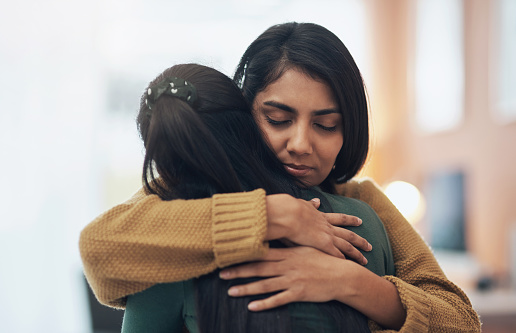 Cropped shot of two young women embracing each other at home