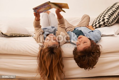 Shot of two young children lying on their backs and reading a book together