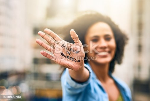 Cropped shot of a woman showing a motivational message written on her hand