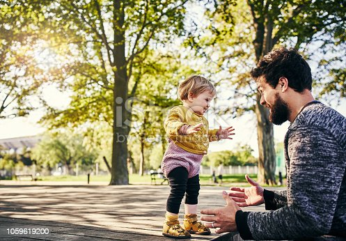 Cropped shot of a young father spending the day in the park with his adorable little daughter