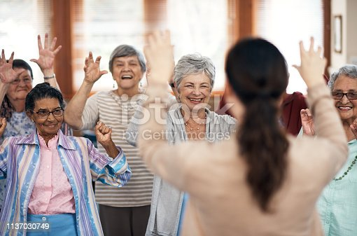 Rearview shot of a female fitness instructor taking a class in an old age home