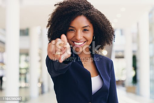 Cropped portrait of an attractive young businesswoman standing and pointing while in the office during the day