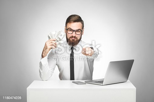 You can earn money! Portrait of handsome satisfied bearded young boss in white shirt and black tie sitting in office, pointing to you finger and holding fan of money,looking at camera, indoor isolated