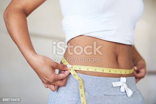 Cropped shot of a young woman measuring her waist in the bathroom