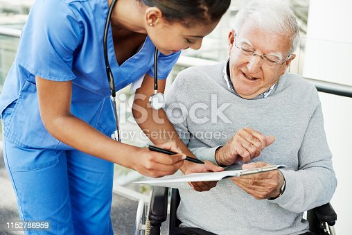 Shot of a young nurse discussing paperwork with an elderly patient in a wheelchair