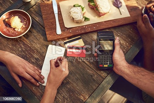 High angle shot of an unrecognizable man ready to pay the bill with his credit card at a cafe