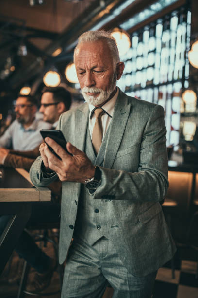 You can reach me anywhere, anytime Senior businessman using phone at the pub old man working in a pub stock pictures, royalty-free photos & images