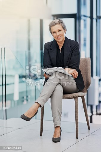 Portrait of a mature businesswoman holding a clipboard while sitting on a chair in an office