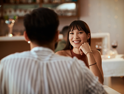 Cropped shot of a young woman smiling while on a date at a restaurant