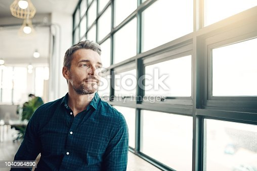 Shot of a mature businessman looking thoughtfully out of an office window