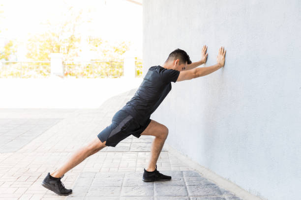 You Can't Achieve Any Goals Without Discipline Determined young Latin man stretching calf while leaning on wall calf stock pictures, royalty-free photos & images