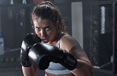 Portrait of a young woman practicing her boxing routine at a gym