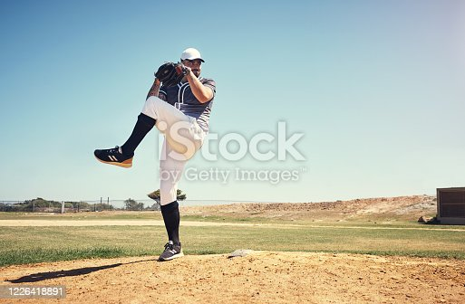 Shot of a young man pitching a ball during a baseball match