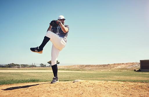 Shot of a young man pitching a ball during a baseball match