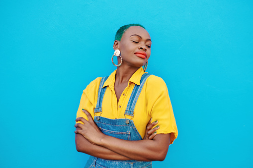 Shot of a beautiful young woman posing against a blue wall