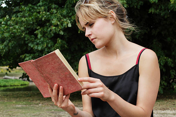 reading a musty old book english outdoor girl - whiteway english outdoor girl stock photos and pictures