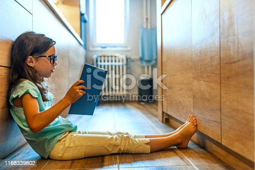 Photo of smiling kid girl sitting at kitchen floor with opened book. Side view of Adorable Cute Girl Reading a book wearing eyeglasses. Storytelling Concept. Side view of pretty little girl reading a book on the floor. Children and education.