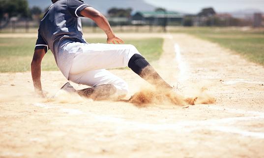 Shot of a young man reaching base during a baseball match