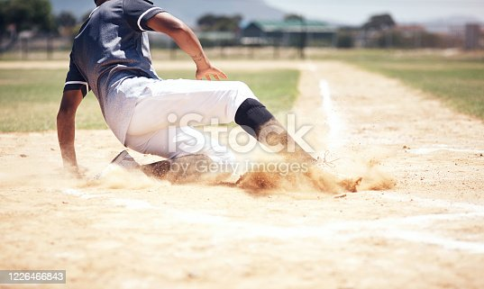 Shot of a young man reaching base during a baseball match