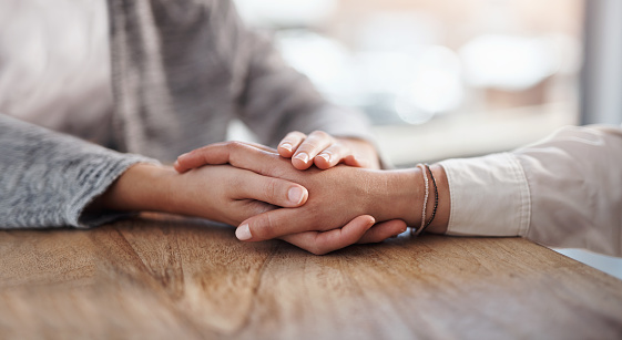 Closeup shot of two unrecognisable people holding hands in comfort