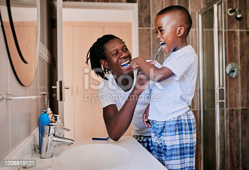 Cropped shot of a young man and his son brushing their teeth in the bathroom at home