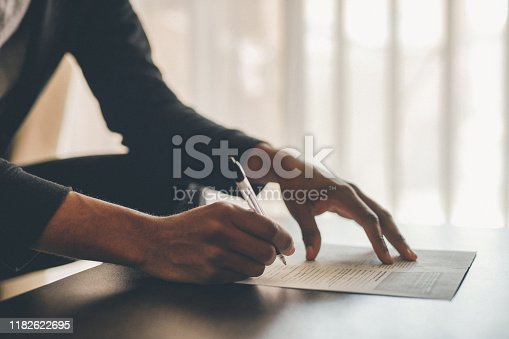 Cropped shot of an unrecognizable man filling out paperwork while doing his budget at home