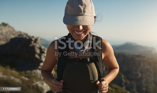 Shot of a young woman hiking up a mountain