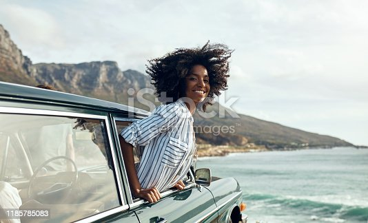Shot of a happy young woman leaning out of a car window on a road trip