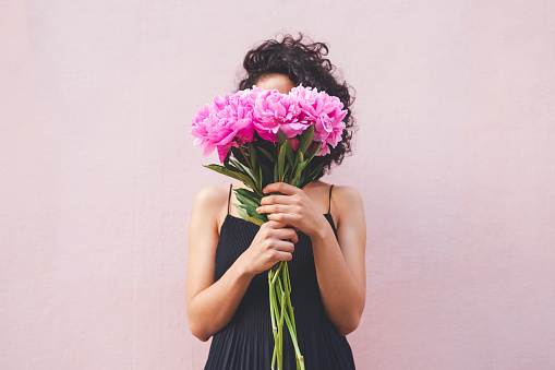 Cropped shot of a woman holding a bouquet of flowers in front of her face