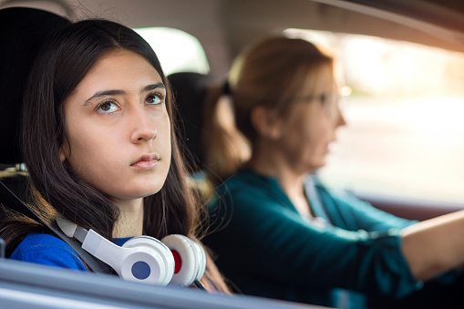 Bad mood teenage girl traveling in a car with her mother