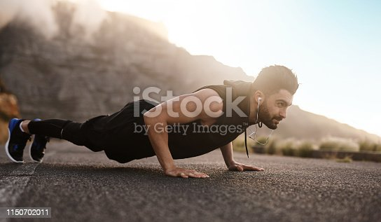 Shot of a sporty young man doing pushups while exercising outdoors