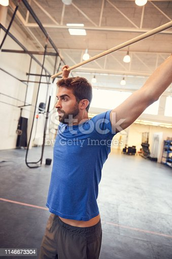 Cropped shot of a handsome young man working out with a stick in the gym