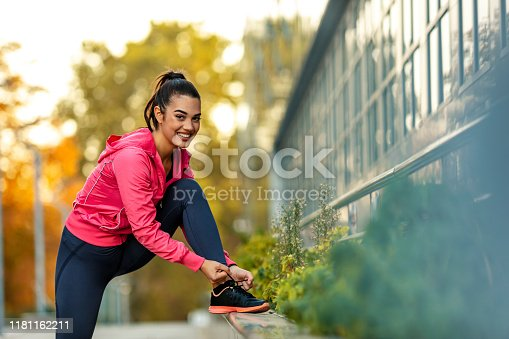 Front view of young beautiful and attractive sport runner woman tying her shoe sneaker laces smiling happy ready for running and jogging workout at city, looking at camera.