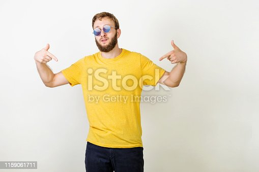 istock You found right guy, pick me. Confident, charismatic bearded male in sunglasses promoting himself pointing at body over gray wall. Man in blank yellow t-shirt pointing at himself. 1159061711