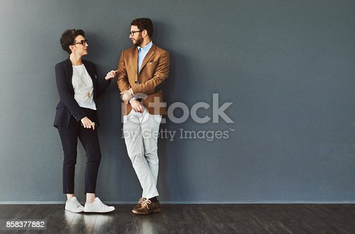 Shot of two designers having a conversation while leaning against a wall